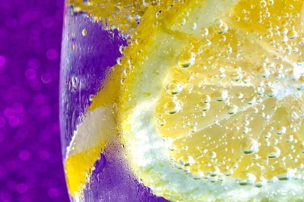 Soda mit zitrone auf purpurrotem makro