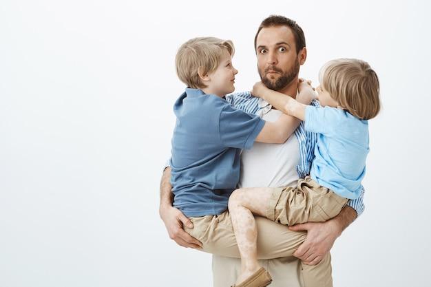Söhne nutzen den liebevollen und fürsorglichen vater. porträt des ahnungslosen lustigen europäischen vaters, der kinder auf händen hält und ahnungslos blickt
