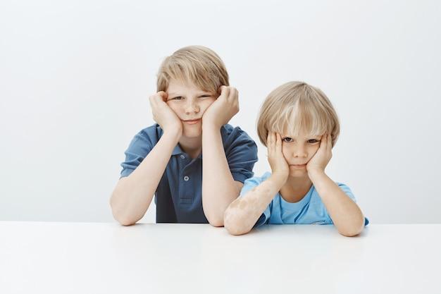 Söhne wegen schlechten benehmens in der schule geerdet. gelangweilte unglückliche niedliche männliche kinder, die am tisch sitzen