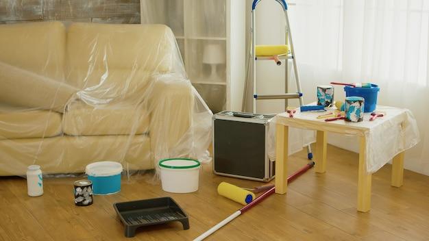 Sofa bedeckt mit plastikfolie während der hausrenovierung. zuhause während der renovierung, dekoration und malerei. instandhaltung von innenwohnungen. rolle, leiter für die hausreparatur