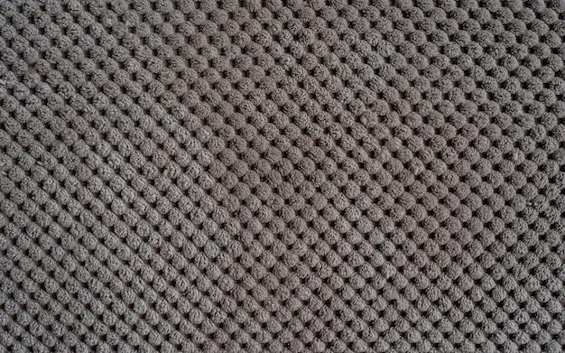 Sofapolsterung nahaufnahme textur aus rauem, dichtem, geripptem stoff beige hintergrund
