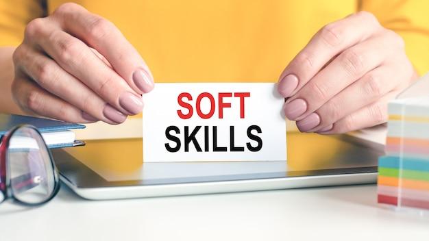 Soft skills sind in den händen einer frau auf eine weiße visitenkarte geschrieben. gläser, tablette und block mit mehrfarbigem papier für notizen.
