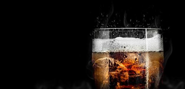 Softdrinkglas mit eisspritzen auf kühlem rauch