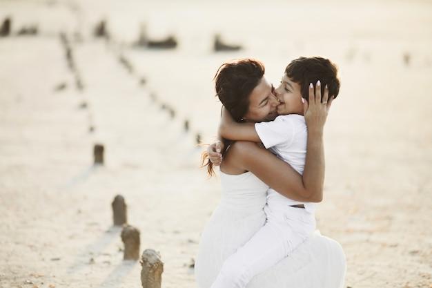 Sohn beißt mutter in die nase und umarmt sie, in weißen kleidern, im sand sitzend