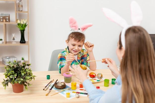 Sohn genießt es, mit seiner mutter eier zu malen