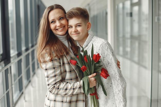 Sohn gibt einer mutter ein paar rote tulpen in einer modernen halle