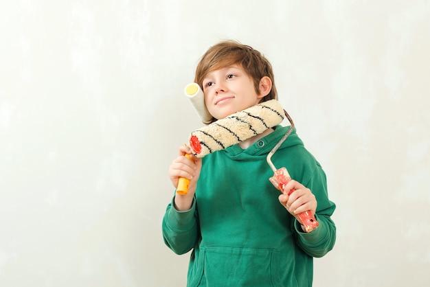 Sohn hilft eltern, wand zu streichen. junge malt die wand mit einer walze.