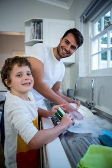 Sohn hilft vater beim waschen von utensilien
