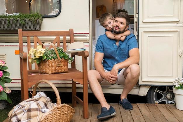 Sohn umarmt seinen vater, während er auf wohnwagen sitzt
