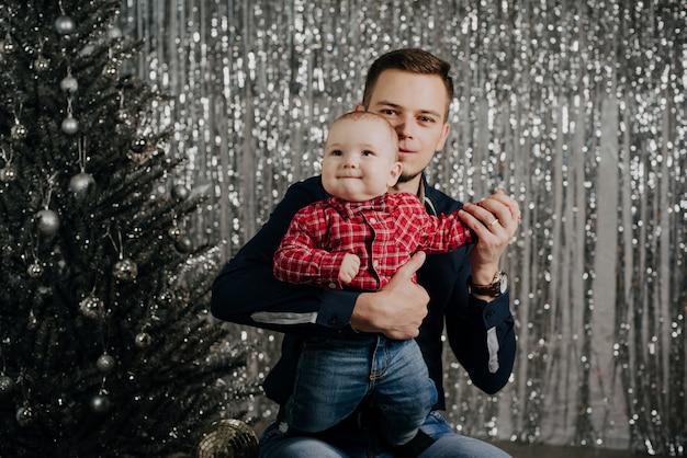 Sohn und vater. ein kleiner junge in den armen seines vaters am weihnachtsbaum