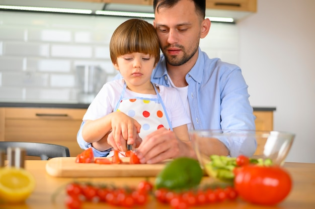 Sohn und vater schneiden tomaten vorderansicht