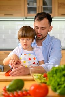 Sohn und vater schneiden tomaten