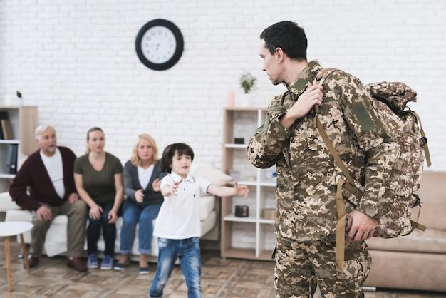 Sohn verabschiedet sich von seinem vater, der zum militärdienst geht.