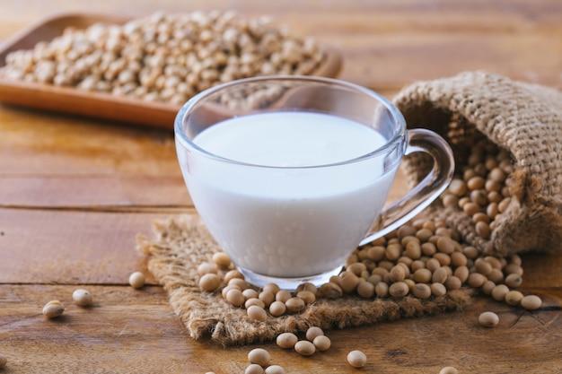 Soja melken mit sojabohnen auf hölzernem hintergrund