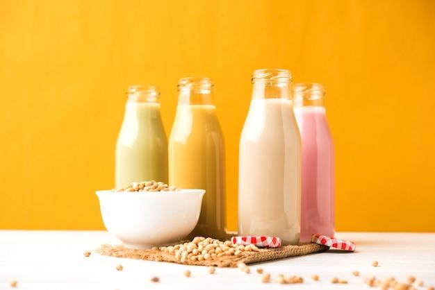 Soja oder sojamilch, die durch einweichen und mahlen von sojabohnen hergestellt wird, ist ein gesundes getränk, das in einer flasche mit rohem ganzen in einer schüssel serviert wird