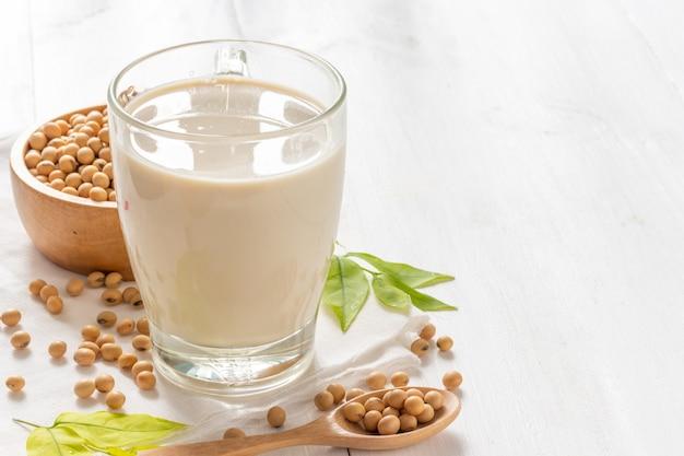 Soja- oder sojamilch in einem glas mit sojabohnen im hölzernen schüsselhintergrund