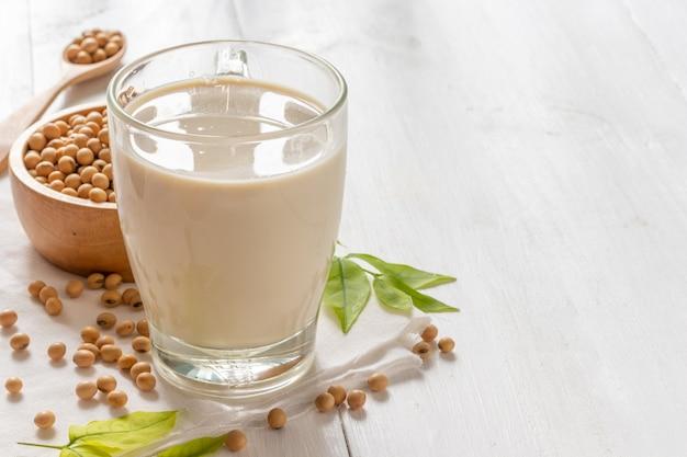 Soja oder sojamilch in glas mit sojabohnen in holzschale