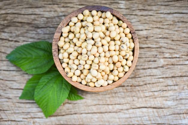 Soja, sojabohne in den landwirtschaftlichen erzeugnissen einer hölzernen schüssel auf dem hölzernen hintergrund / den trockenen sojabohnenölbohnen und dem grünen blatt