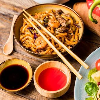 Soja- und rote chili-saucenschüssel mit udon-nudeln und essstäbchen über dem tisch