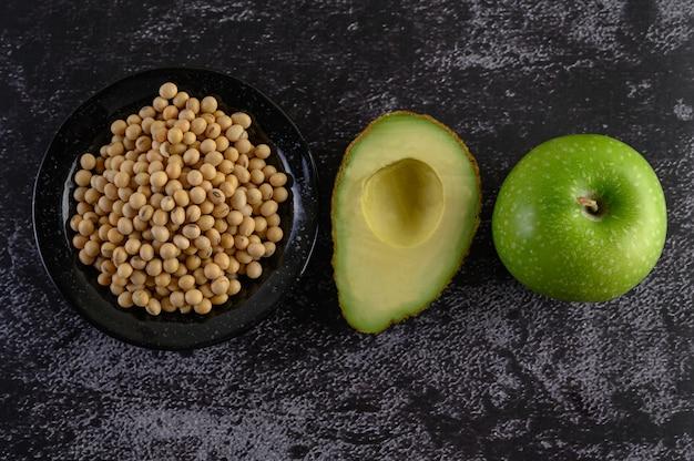 Sojabohne, avocado und apfel auf einem schwarzen zementboden.