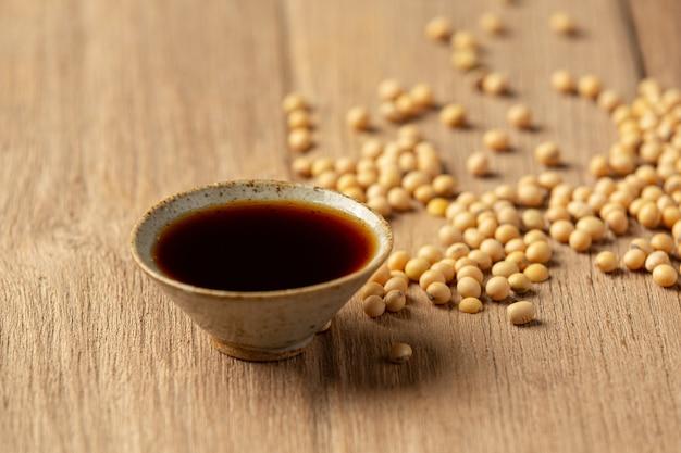 Sojabohnensauce und sojabohne auf holzboden sojasauce lebensmittelernährungskonzept.