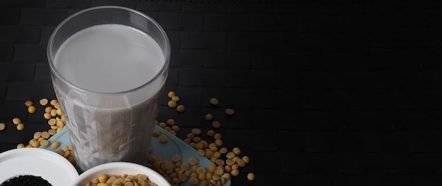 Sojamilch gemischt mit schwarzem sesam in klarglas auf schwarzem teller matt schwarzer sesam und sojabohnen