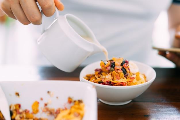 Sojamilch in acai-schüssel mit frischer mango, avocado, banane, beeren, sonnenblumenkernen, chiasamen und müsli gießen. superfood frühstücksschale für gesunde und vegane menschen.
