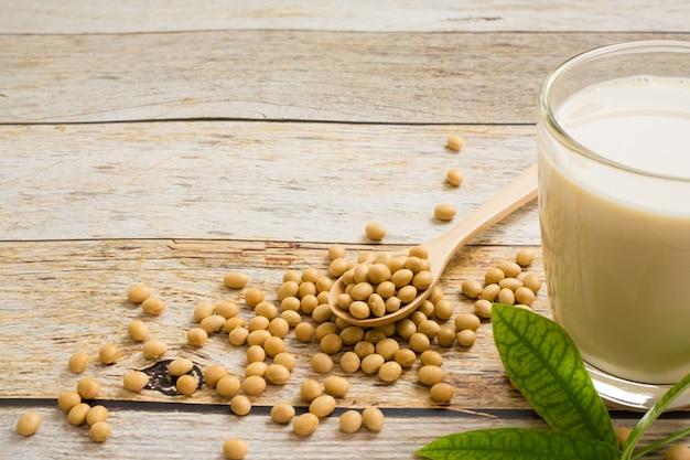 Sojamilch und sojabohne es auf holztabellenhintergrund, gesundes konzept. vorteile von soja.