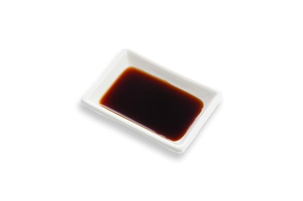 Sojasauce in einer weißen rechteckigen sauciere. würze für sushi. weißer hintergrund. isoliert.