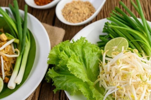 Sojasprossen, salate, limetten- und frühlingszwiebeln in weißer platte auf holztisch