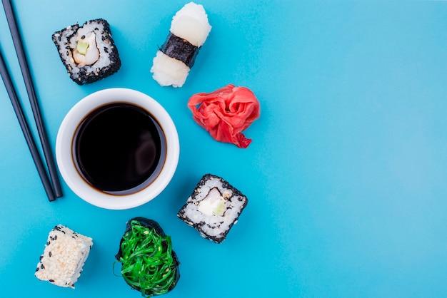 Sojasuppe mit sushi rollt herum