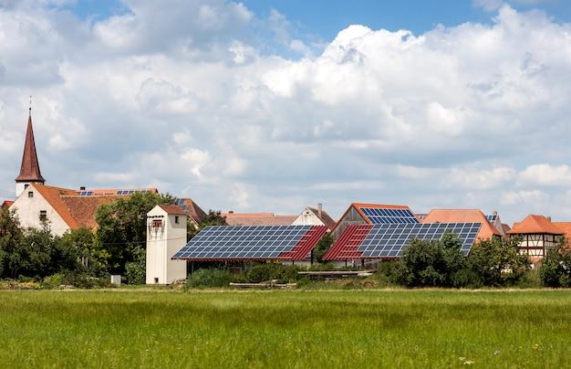 Solarbetriebene häuser in einem ländlichen dorf in deutschland. sonnenkollektoren auf dem dach als alternative energiequelle.