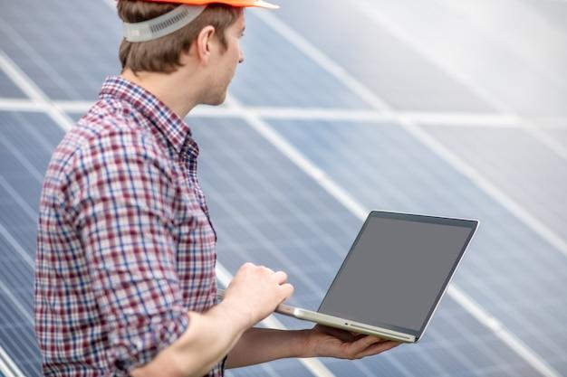 Solarenergie. mann im karierten hemd mit laptop in den händen, der auf die oberfläche der nebenstehenden solarbatterie schaut