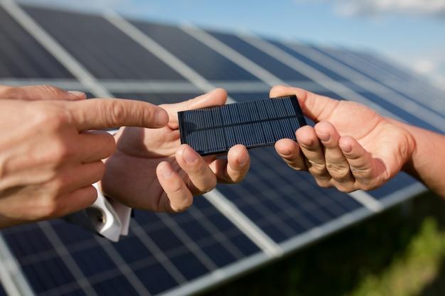 Solarenergie, zwei hände, die photovoltaisches einzelteil halten.