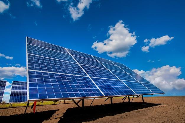 Solarenergiestations-paneelsystem auf gepflügtem feld und himmel mit wolken