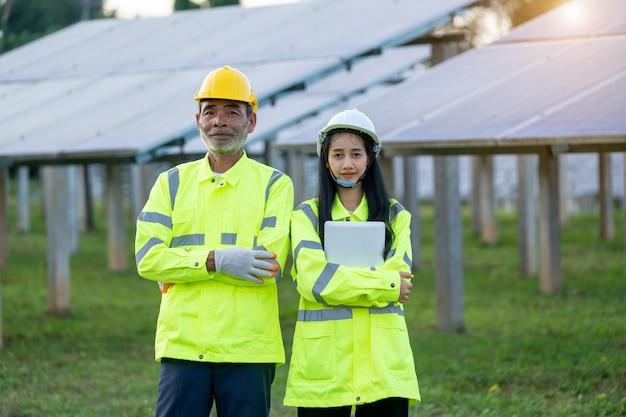 Solarkraftwerk, ingenieur, der mit tablet-computer bei solar panels arbeitet.