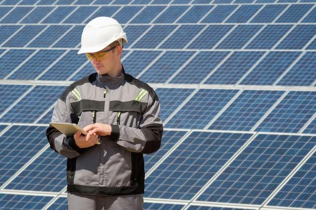 Solarmodulingenieur oder arbeiter, der tablette betrachtet und betrieb in der nähe des solarmodulfeldes überprüft. heißes sonniges sommerwetter