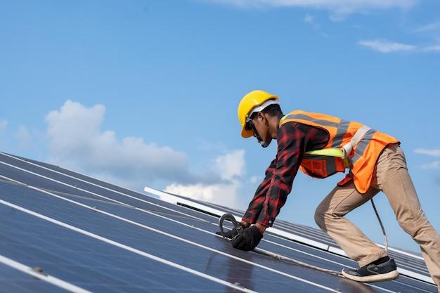 Solarpanel-techniker mit bohrer, der sonnenkollektoren auf dem dach auf dem solarpanel-feld installiert, umweltschutz, alternatives konzept für saubere grüne energie.