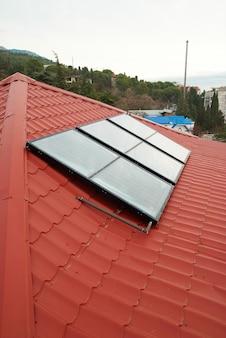 Solarwasserheizung auf dem roten hausdach.