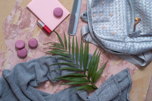 Solatecollection des sommers auf einem rosa hintergrund. kleid, graue metallfarbe tasche, kamm, makronen und kosmetik-lippenstift und nagellack.