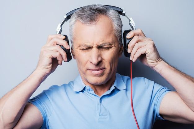Solche musik ist nichts für mich. porträt eines frustrierten älteren mannes mit kopfhörern, der musik hört und die augen geschlossen hält, während er vor grauem hintergrund steht