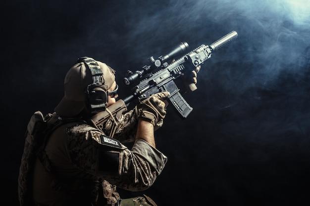 Soldat der besonderen kräfte mit gewehr auf dunkelheit