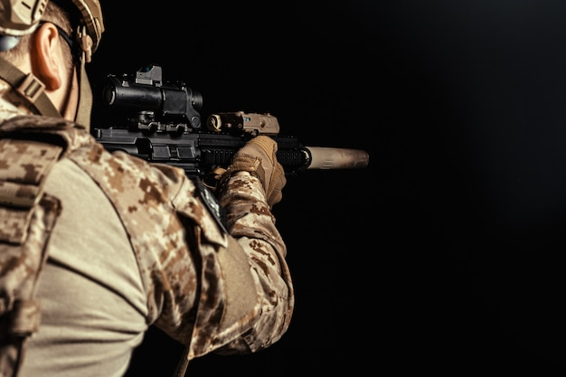 Soldat der besonderen kräfte mit gewehr auf dunklem hintergrund