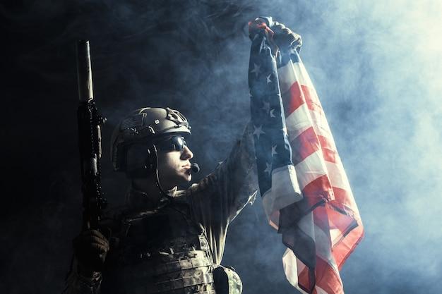Soldat, der maschinengewehr mit staatsflagge hält