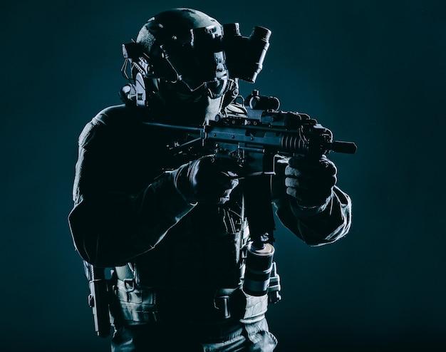 Soldat des spezialeinsatzkommandos der armee, mitglied des polizei-terrorismus-angriffsteams, sicherheitsdienstschütze in maske, helm mit kopfhörer und nachtsichtgerät, bewaffnetes kurzrohr-servicegewehr