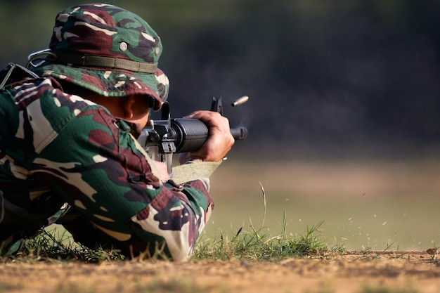 Soldat feuert gewehrgewehr ab, um mit kugelpatrone in der luft zu zielen