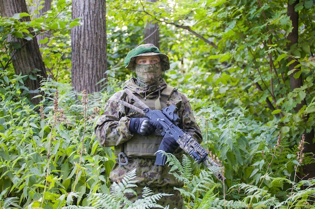 Soldat im wald mit einem maschinengewehr. aus- und weiterbildung von soldaten
