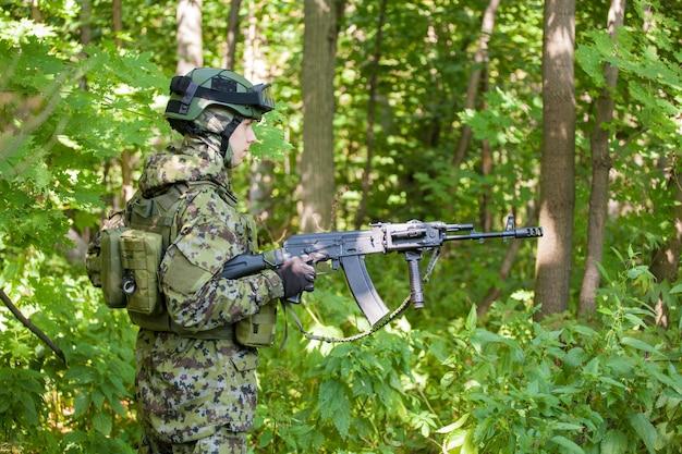 Soldat im wald mit einem maschinengewehr. ausbildung des militärs für den kampf.
