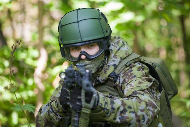 Soldat im wald mit einem maschinengewehr. vorbereitung des militärs auf feindseligkeiten. das maschinengewehr zielt