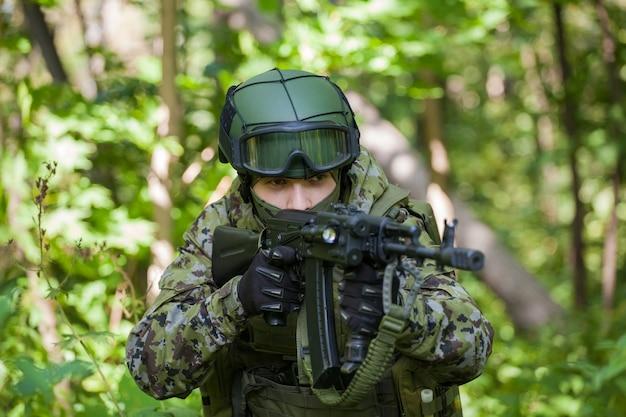 Soldat im wald mit einem maschinengewehr. vorbereitung des militärs auf feindseligkeiten